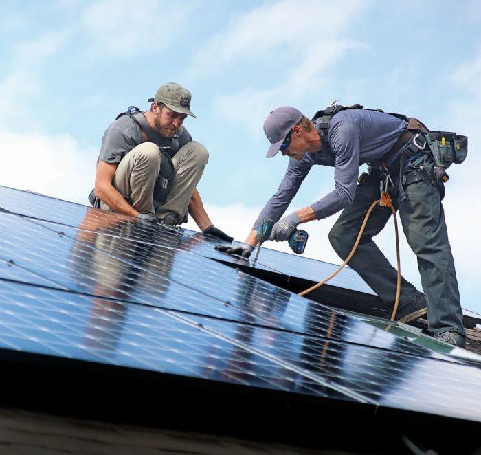 εργάτες σε στέγη με φωτοβολταϊκά
